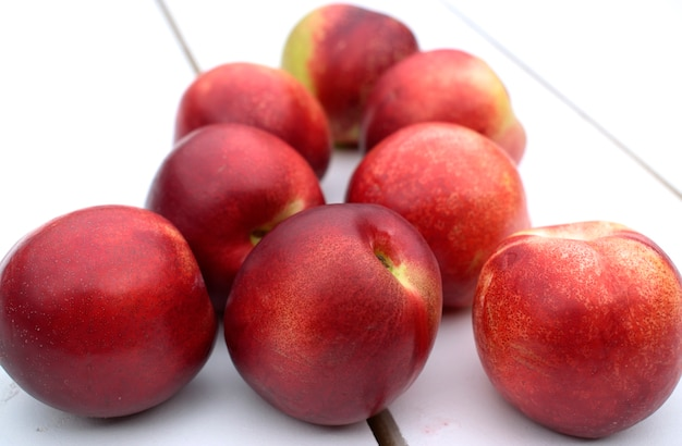 Fresh and ripe nectarines on white wooden table.