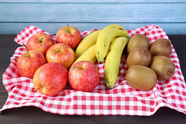 Fresh ripe nutritious fruits on a tray with checkered clothed on the wooden rustic table