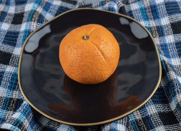 Свежий спелый апельсин на черной тарелке.