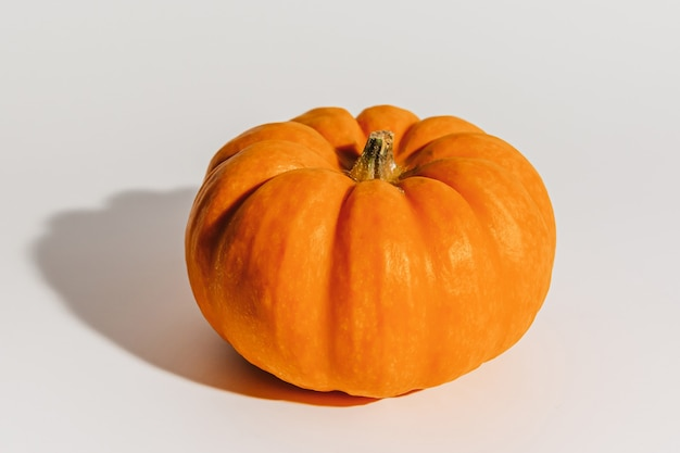 白い背景の上の新鮮な熟したオレンジ色のカボチャ。テキストモックアップハロウィーンのコンセプトのためのスペース