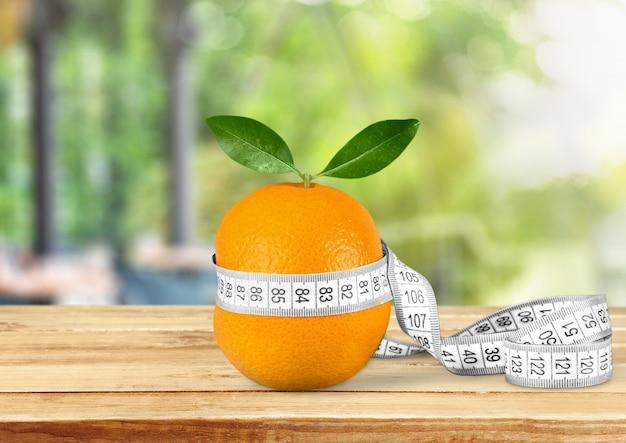 Свежий спелый апельсин с рулеткой
