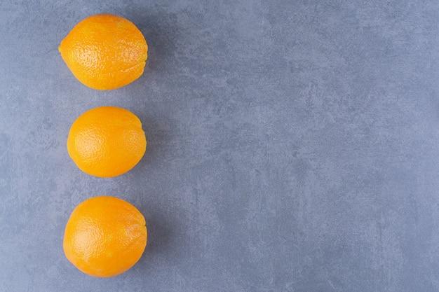 Fresh ripe oranges on the dark surface