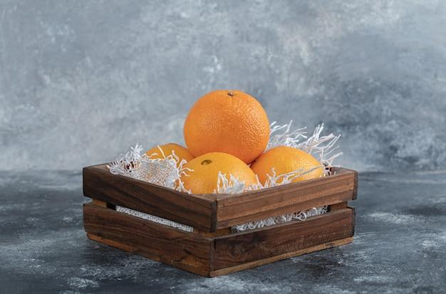 Свежие спелые апельсины в деревянной коробке.