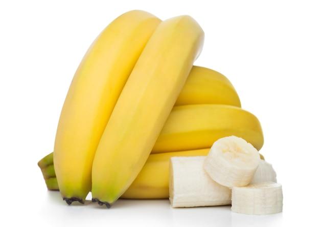 白い表面にスライスされた断片を持つ新鮮な熟した有機バナナクラスター