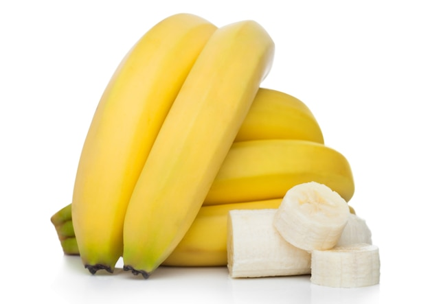 Fresh ripe organic bananas cluster with sliced pieces on white surface
