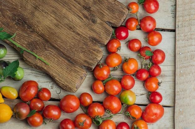 Свежие спелые органические садовые помидоры на деревянном столе