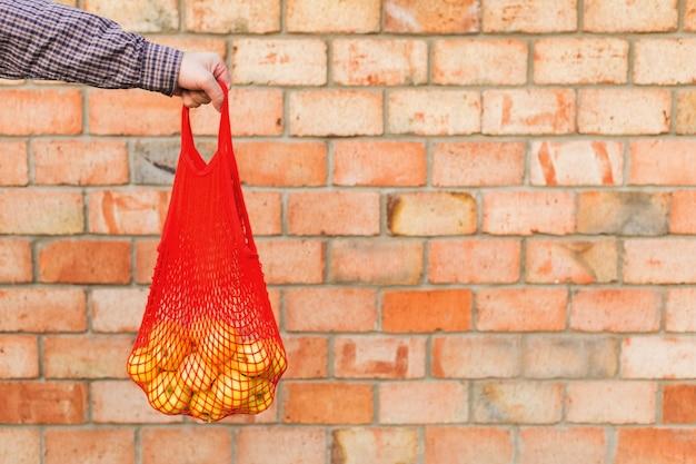 食品やリンゴジュースの男性の手でメッシュバッグをショッピングで新鮮な熟した有機青リンゴ。