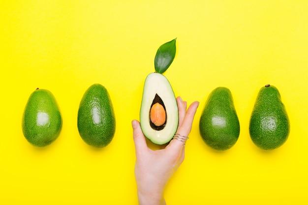 Свежий зрелый органический зеленый авокадо в женской руке с кольцом на предпосылке цвета, концепции еды лета взгляд сверху. минимальный плоский стиль лежал авокадо целый фрукт на желтом фоне.