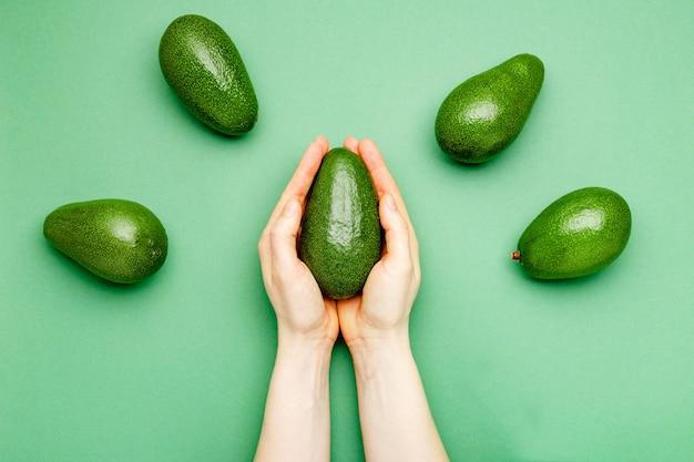 女性の手で新鮮な熟したオーガニックグリーンアボカド色背景、トップビュー夏の食品のコンセプト。最小限のフラットレイアウトスタイルアボカド全体のフルーツミントグリーンの背景に。
