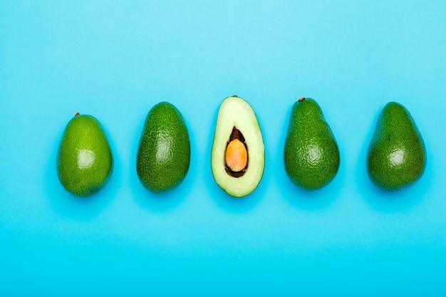 新鮮な熟した有機緑のアボカドと青い色の背景、平面図夏の食品のコンセプトの半分。最小限のフラットレイアウトスタイルアボカド全体のフルーツとミントグリーンの背景に半分。