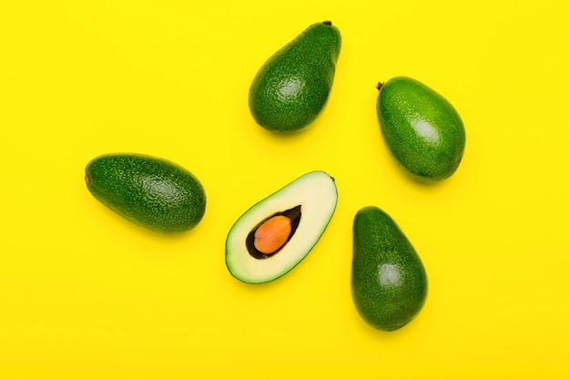 Fresh ripe organic green avocados and halve on color yellow background