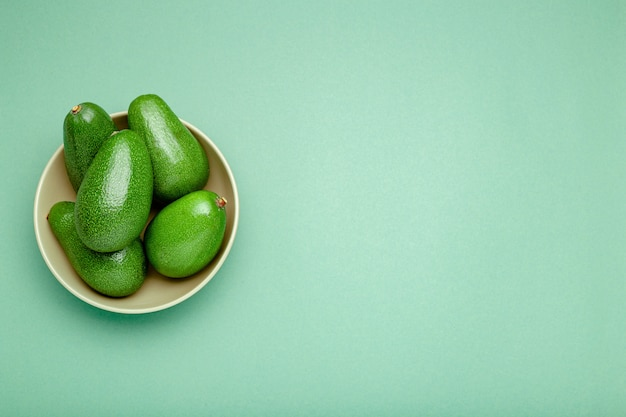 Свежие зрелые органические зеленые авокадоы в плите на предпосылке цвета, концепции еды лета взгляд сверху. минимальный плоский стиль лежал авокадо целый фрукт на мятно-зеленый фон с копией пространства для текста.