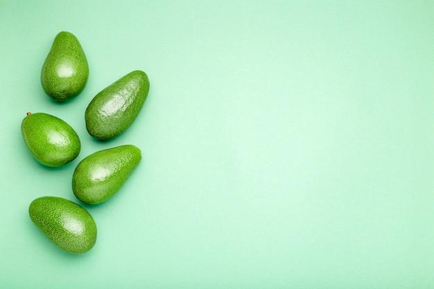 色の背景、トップビューの夏の食品のコンセプトに新鮮な熟した有機緑アボカド。テキストのコピースペースとミントグリーンの背景に最小限のフラットレイアウトスタイルアボカド全体のフルーツ。