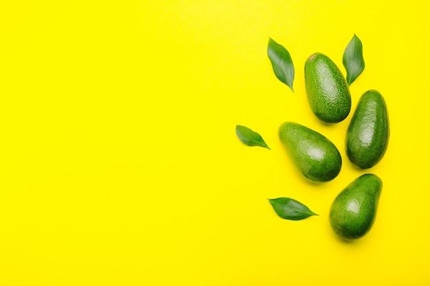 Свежие спелые органические зеленые авокадо с листьями на цветном желтом фоне