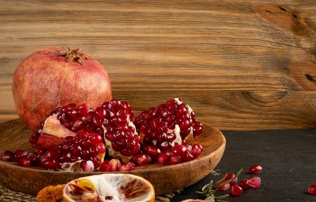 Свежие спелые органические плоды граната с сочными семенами на деревенской скатерти из мешковины
