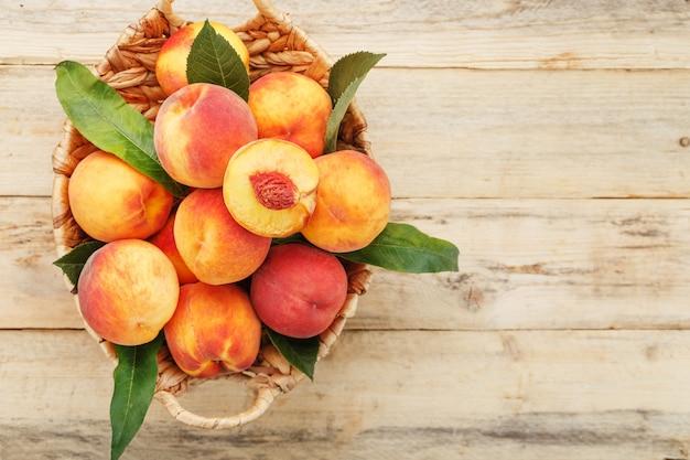 木製のテーブルの枝編み細工品バスケットで新鮮な熟した桃