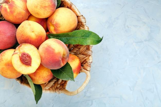 籐のかごの中の新鮮な熟した桃