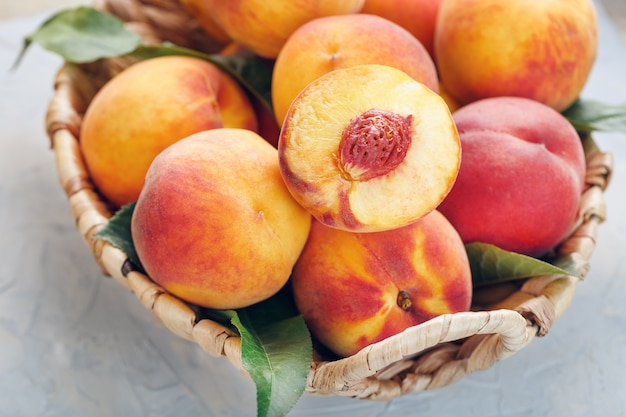 Fresh ripe peaches in a wicker basket