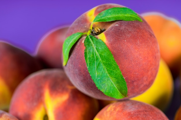 Fresh, ripe peaches with leaves close up