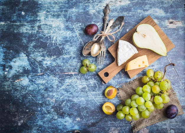 Свежая спелая груша, ассорти из сыров, виноград, сливы в миске