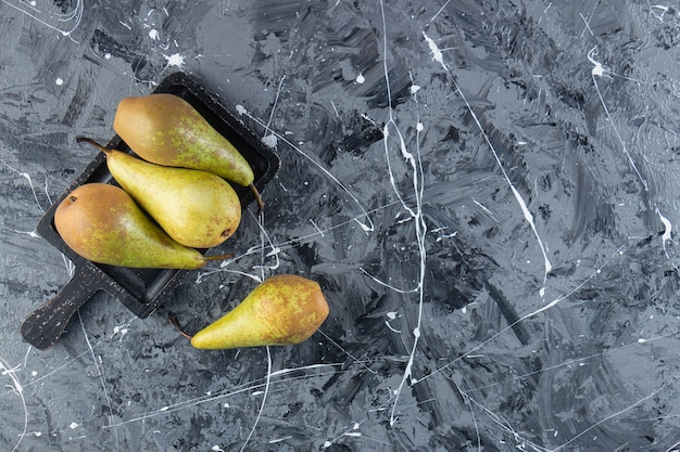 Fresh ripe pears on a wooden board placed on marble background .