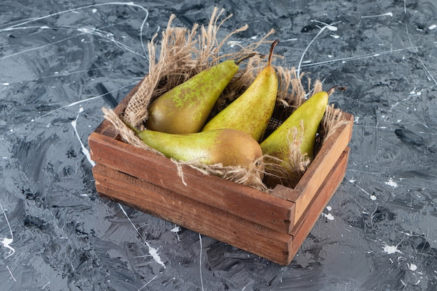 Fresh ripe pears in a wooden old box placed on marble surface .