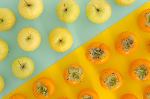 Fresh ripe persimmons,apples bright split background. flat lay