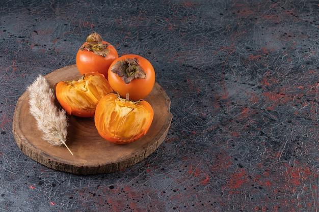 Свежие спелые хурмы с колосом пшеницы, помещенные на деревянный кусок