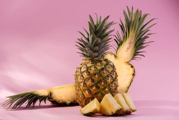 ピンクの背景に新鮮な熟したパイナップルと果物のカットスライス。こんにちは、夏または夏のシーズンセールコンセプトバナー。