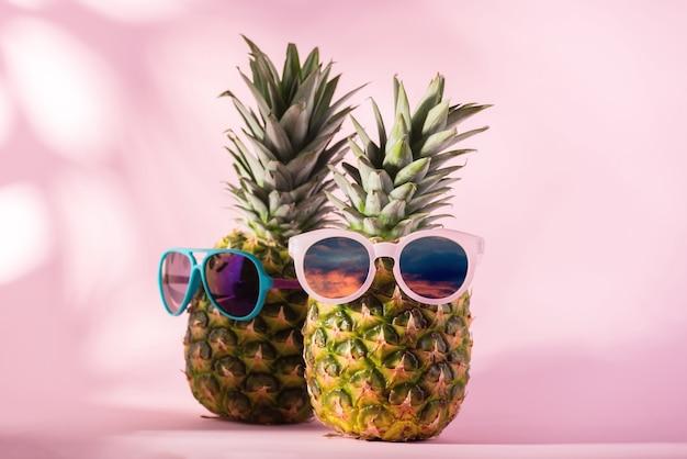 ピンクの背景にサングラスをかけた新鮮な熟したパイナップル。こんにちは、夏または夏のシーズンセールコンセプトバナー。