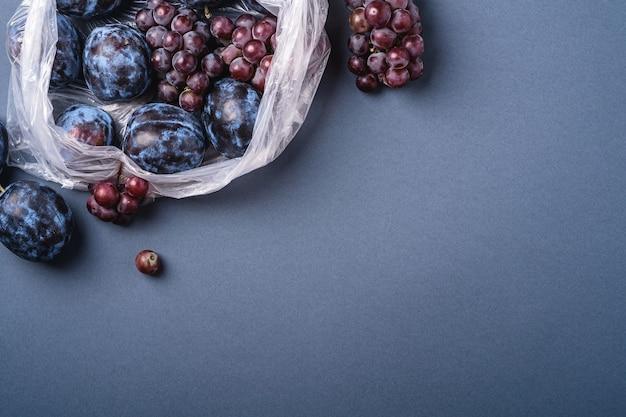 Свежие спелые плоды сливы и виноградные ягоды в полиэтиленовом пакете на минимальном сине-сером фоне, пространство для копирования сверху
