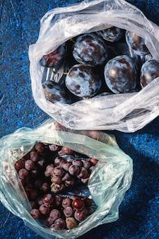 Свежие спелые плоды сливы и виноградные ягоды в полиэтиленовом пакете
