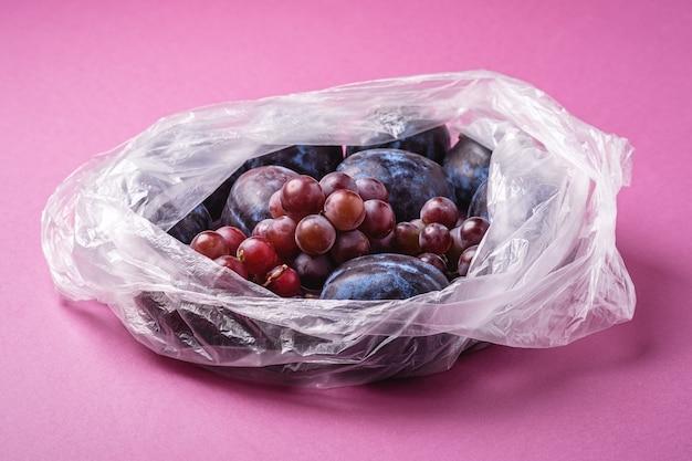 비닐 봉지 패키지에 신선한 익은 자두 과일과 포도 열매