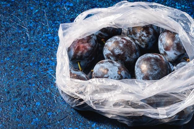 Свежие спелые плоды сливы в полиэтиленовом пакете на синем абстрактном столе, угловой вид