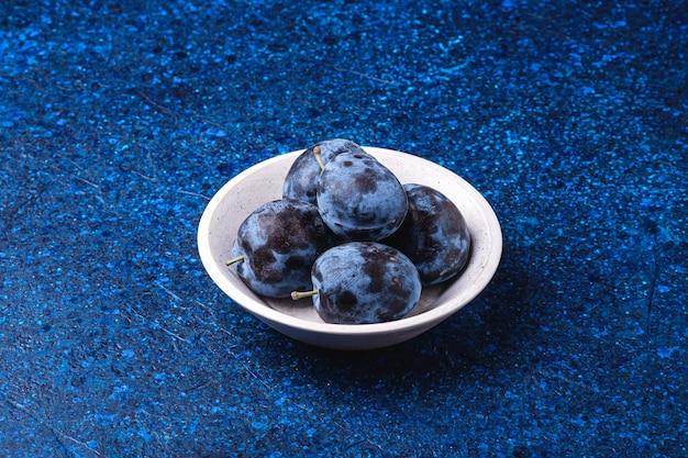 Свежие спелые плоды сливы в белой деревянной миске на синем абстрактном столе, угловой вид