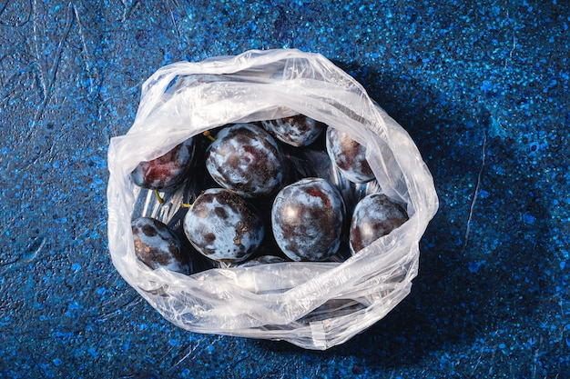 Fresh ripe plum fruits in plastic bag package on blue abstract background, top view