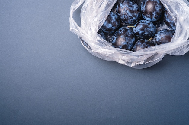 Fresh ripe plum fruits in plastic bag package on blue grey minimal