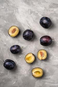 Свежие спелые плоды сливы целиком и нарезанные с каплями воды на каменном бетонном фоне, вид сверху