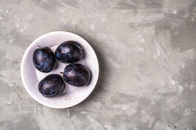 Свежие спелые плоды сливы с каплями воды в деревянной миске на каменном бетонном фоне, вид сверху копией пространства