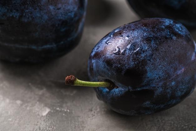 Свежие спелые плоды сливы с каплями воды на каменном бетонном столе, макрос углового обзора