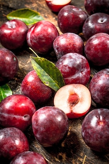 Fresh, ripe plums with leaves. on a wooden background.