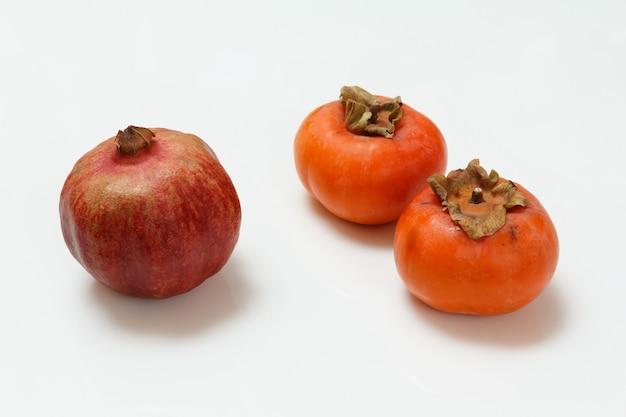 흰색 표면에 신선한 익은 석류와 감 과일