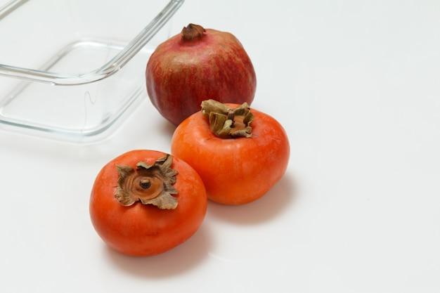 잘 익은 신선한 석류, 감 과일 및 흰색 표면에 유리 그릇