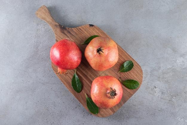 Свежие спелые гранаты с листьями на деревянной разделочной доске.