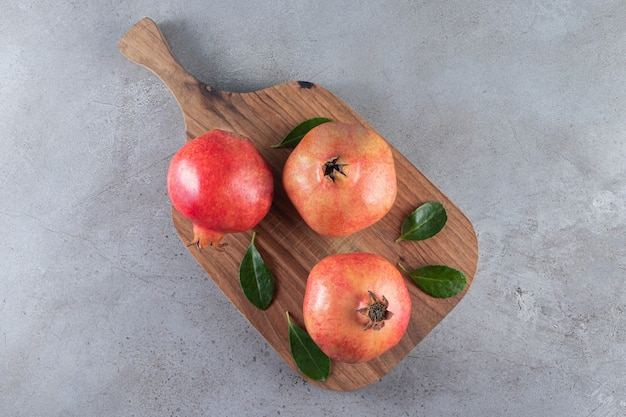 Fresh ripe pomegranates with leaves placed on a wooden cutting board .