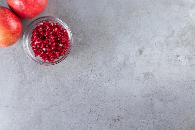 씨앗과 신선한 익은 석류 돌 배경에 배치합니다.