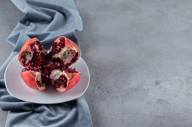 白い皿に置かれた種子と新鮮な熟したザクロ。
