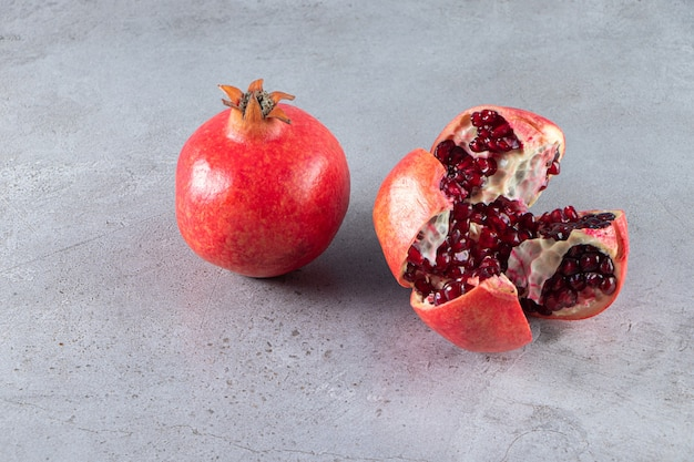 Fresh ripe pomegranates with seeds placed on stone background.