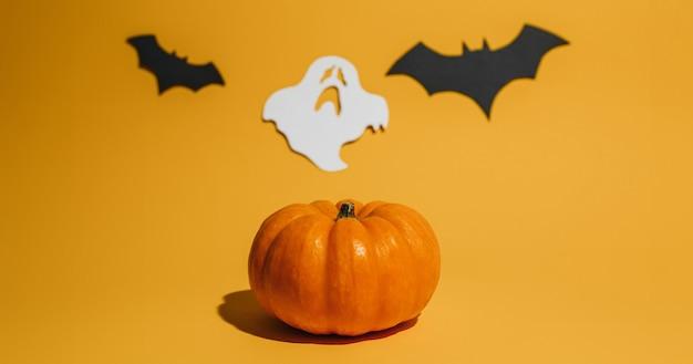 オレンジ色の背景に新鮮な熟したカボチャ。コウモリと幽霊のハロウィーンのコンセプトとスペース