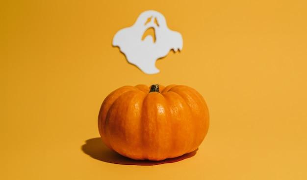 オレンジ色の背景に新鮮な熟したカボチャ。ゴーストハロウィンコンセプトの空間